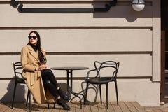 Schot van aanbiddelijke jonge donkerbruine vrouw die modieuze laagzitting dragen bij lijst in straat openluchtkoffie en koffie of stock afbeeldingen