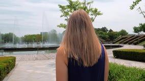 Schot van de Steadicam het achtermening van een mooi jong meisje die in blauwe kleding in het park aan de fontein lopen stock video