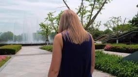 Schot van de Steadicam het achtermening van een mooi jong meisje die in blauwe kleding in het park aan de fontein lopen stock footage