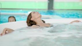 Schot van een ontspannen vrouw in zwarte bikini in een hete ton stock footage