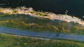 Schot van hierboven van een zwarte autoritten op een gebied langs een landelijke weg dichtbij een klip bij de kust bij zonsonderg stock footage