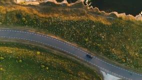 Schot van hierboven van een zwarte autoritten op een gebied langs een landelijke weg dichtbij een klip bij de kust bij zonsonderg stock videobeelden