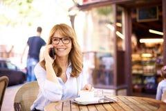 Schot van midden oude vrouwenzitting in koffiewinkel en het telefoneren van stock afbeeldingen