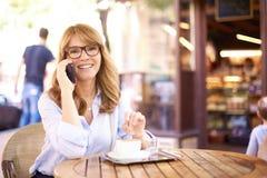Schot van midden oude vrouwenzitting in koffiewinkel en het telefoneren van royalty-vrije stock fotografie