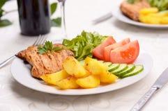 Schotel met geroosterd varkensvleeslendestuk, salade en aardappels Stock Afbeeldingen