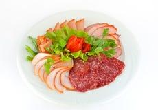 Schotel met pastrami en salamiplakken op wit worden geïsoleerd dat. Stock Foto's