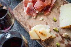 Schotel met Spaanse ham jamon serrano of Italiaanse prosciuttocrudo, gesneden Italiaanse harde kaas, glazen rode wijn Stock Fotografie