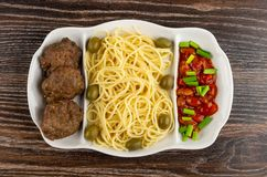 Schotel met spaghetti, kotelet, bonen, groene ui en olijven op lijst Hoogste mening royalty-vrije stock afbeeldingen