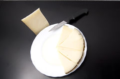 Schotel met wiggen van kaas en olie stock fotografie