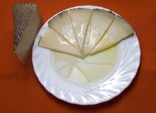 Schotel met wiggen van kaas en olie stock foto's