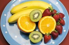 Schotel van fruit - bananen, sinaasappel, kiwifruit en aardbeien Stock Foto's