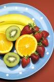 Schotel van fruit - bananen, sinaasappel, kiwifruit en aardbeien - verticaal Royalty-vrije Stock Afbeeldingen