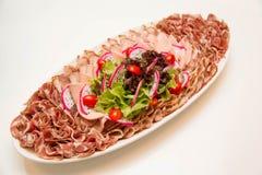 Schotel van gemengde fijne vleeswaren op wit Stock Fotografie