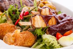 Schotel van gemengde vlees, salade en Frieten stock afbeeldingen