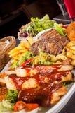 Schotel van gemengde vlees, salade en Frieten stock foto