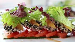 Schotel van het luxe diende de dure restaurant met zoete aromatische broodjes met sesamzaden met oranje en verse salade stock videobeelden