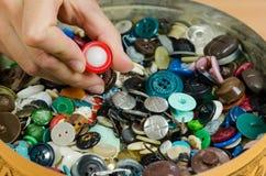 Schotel van kleurrijke knopen en vingeroogst Stock Foto