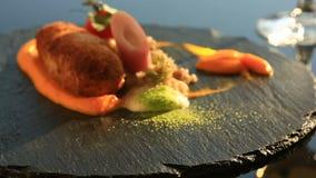Schotels bij het gastronomische restaurant Close-up De kotelet van konijnenvlees met versiert van groen boekweit stock videobeelden