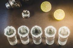 Schoten van tequila en stukken van de donkere achtergrond van kalkona/schoten van tequila en stukken van de donkere achtergrond v royalty-vrije stock fotografie