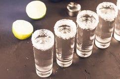 Schoten van tequila en stukken van de donkere achtergrond van kalkona/schoten van tequila en stukken van de donkere achtergrond v stock afbeeldingen