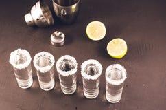 Schoten van tequila en stukken van kalk en schudbeker/schoten van tequila en stukken van kalk en schudbeker op een donkere achter stock afbeeldingen