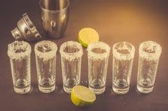 Schoten van tequila en stukken van kalk en schudbeker/schoten van tequila en stukken van kalk en schudbeker op een steenachtergro stock fotografie