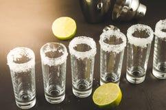 Schoten van tequila en stukken van kalk en schudbeker/schoten van tequila en stukken van kalk en schudbeker op een steenachtergro royalty-vrije stock fotografie