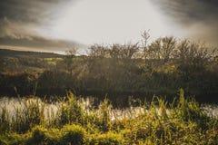 Schots Dramatisch Hemellandschap met Riviergras en Krachtige zon royalty-vrije stock foto