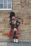 Schotse pijpermens die zich in Schotse traditionele geruit Schots wollen stofkilt kleden die bagpiper spelen bij Koninklijke Mijl stock afbeelding
