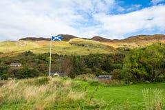 Schotse vlag die in de wind dichtbij het kasteel van Eilean golven Donan Stock Foto's