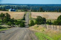 Schotterstraße unter Bauernhoffeldern in Ost-Oregon Stockfotografie