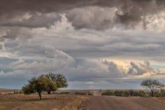 Schotterstraße unterwegs zur namibischen Wüste mit extrem drastischem Himmel, Sturm stockbild