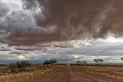Schotterstraße unterwegs zur namibischen Wüste mit extrem drastischem Himmel, Sturm stockbilder