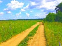 Schotterweg auf einem Gebiet am sonnigen Tag Lizenzfreie Stockfotos