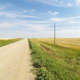 Schotterweg durch Ackerland Lizenzfreie Stockfotos