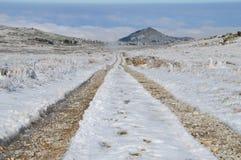 Schotterweg in einem hohen Bergplateau Snowy Stockfotografie