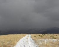 Schotterweg in einem Snowy-Bergplateau Lizenzfreie Stockbilder