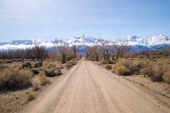 Schotterweg führt, um zu schneien bedeckte Sierra Nevada -Berge in Sprin Lizenzfreie Stockfotos