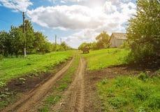 Schotterweg im Dorf, im Frühlingstag und im grünen Gras herum Stockfotos