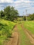 Schotterweg im Dorf, im Frühlingstag und im grünen Gras herum Lizenzfreies Stockfoto