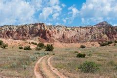 Schotterweg mit zwei Bahnen, die in den Abstand durch eine grasartige Wiese zu den hohen roten Felsenklippen nahe Abiquiu, New Me stockbilder