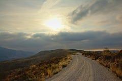 Schotterweg throug Sierra Nevada -Berge mit dem dunklen Bedrohen bewölkt sich stockfotografie