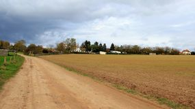 Schotterweg und Ackerland mit Regen-Wolken Lizenzfreie Stockbilder
