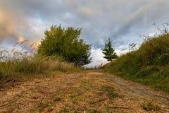 Schotterweg und dichte Wolken Lizenzfreies Stockfoto