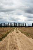 Schotterweg unter Feldern Lizenzfreie Stockbilder