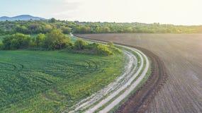 Schotterweg zwischen zwei Landwirtschafts-Feldern Stockfotografie