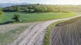 Schotterweg zwischen zwei Landwirtschafts-Feldern Lizenzfreie Stockbilder