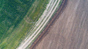 Schotterweg zwischen zwei Landwirtschafts-Feldern Stockbilder