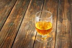 Schottisch auf hölzernem Hintergrund mit copyspace. Eine alte und Weinlesetabelle mit Glas Alkohol. Lizenzfreie Stockfotos