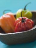 Schottische Mütze-Paprikas in einem hölzernen Teller stockfoto
